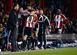 The players all jump on their manager in celebration